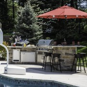 This poolside outdoor kitchen in Chesterfield has a masonry base, granite counter, bar height seating area, Napoleon grill, True outdoor refrigerator, storage and more!