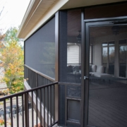The exterior of an outdoor screen room addition with a door and a doggy door
