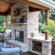custom outdoor room fireplace with a built in grill and wood shelf