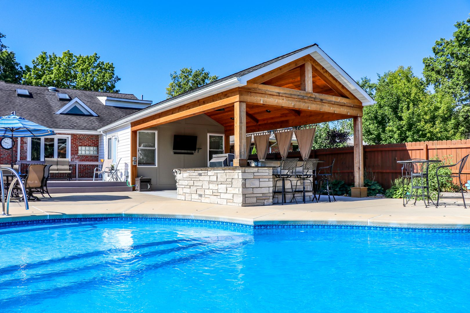 pool side outdoor room with an outdoor kitchen feature that has seating for up to five people