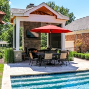 Pool side outdoor room with a beautiful fireplace feature and stone wall in the back