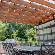 pergola next to a retractable screen room system located on a deck