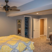 An unfinished portion of a basement transformed into a beautiful large bedroom with a spacious walk in closet