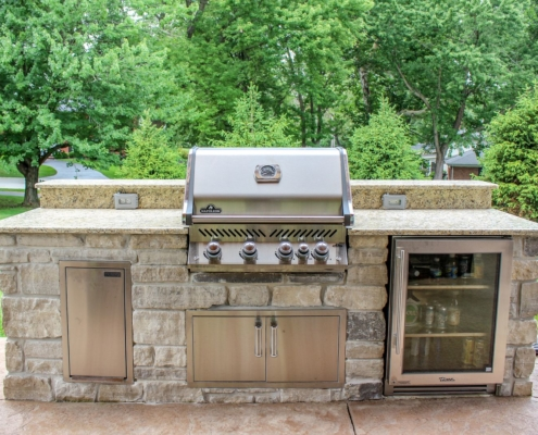 custom built in napoleon grill with a true refrigerator and stainless steel cabinets