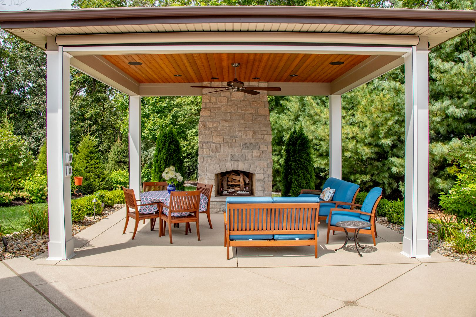 Comfortable seating in a fully retractable screen room that includes a fireplace