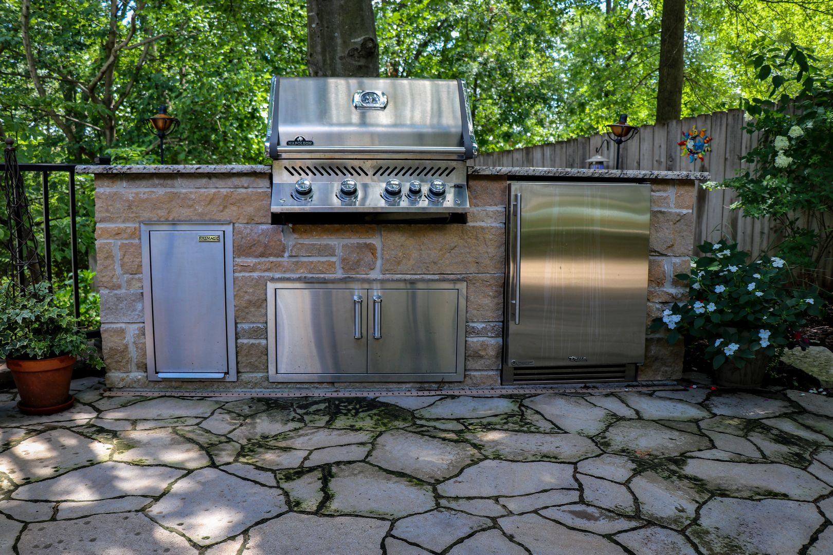 A grilling and beverage center located on a stone patio