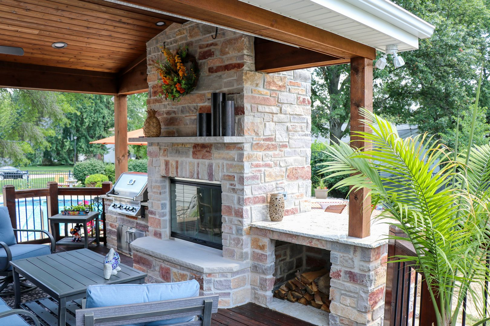 An outdoor room with a beautiful fireplace with firewood storage