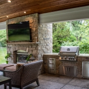 Outdoor kitchen next to a fireplace